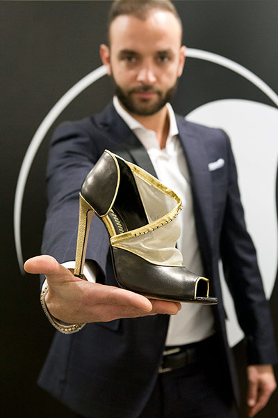 Student with a shoe prototype in hand